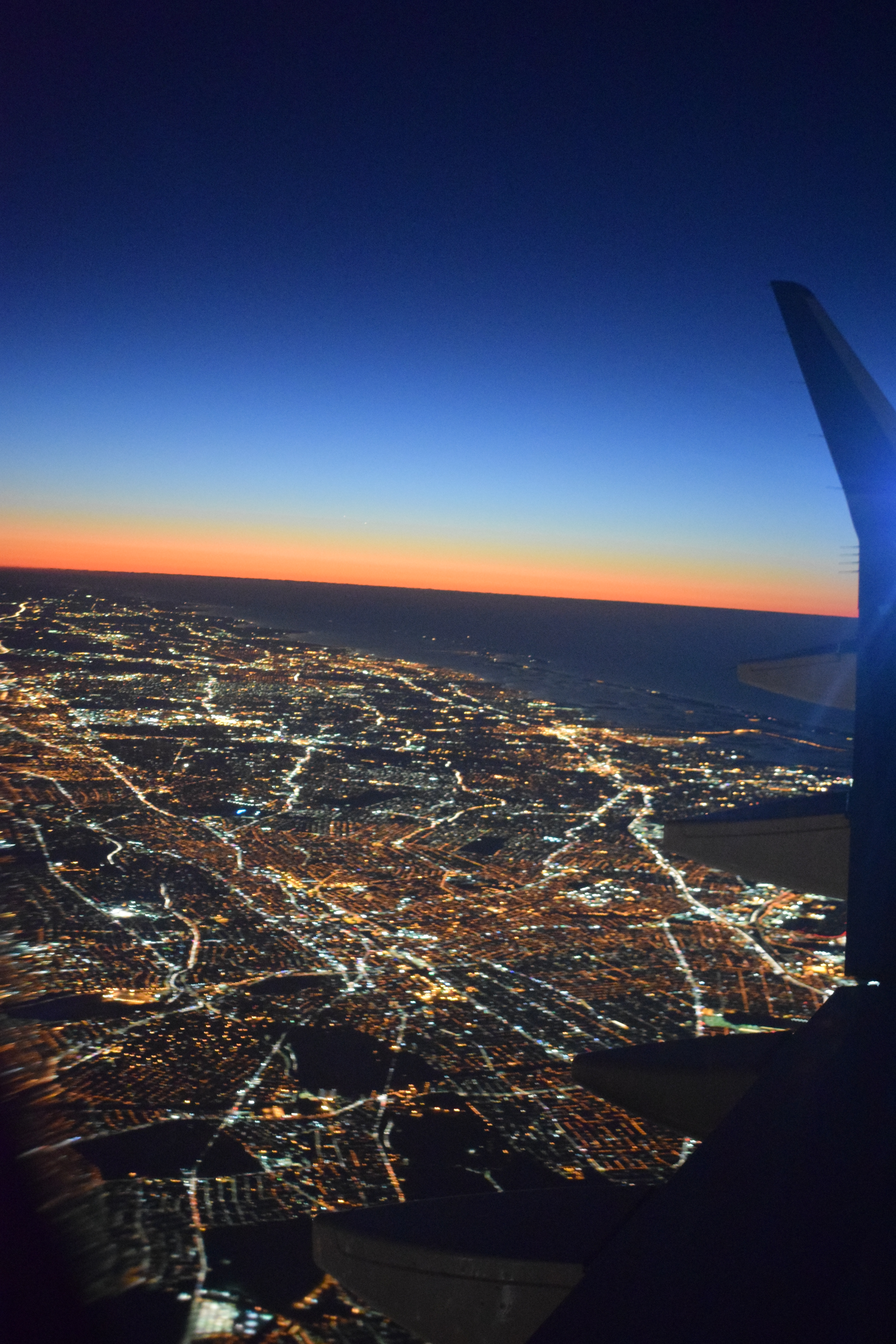 Phenomenal evening aerial view of New York City from 6000 feet above on a plane and sunset in the horizon.